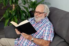 Retired man reading a book in his home Royalty Free Stock Image