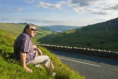 Retired man resting near the road Stock Images