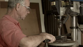 Retired Man 50s-60s working indoors in hobby shed or workshop with carpentry pow. Man working indoors in hobby shed or workshop with tools used in carpentry or stock video