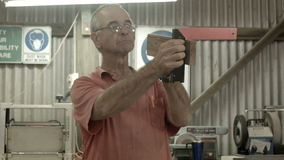 Retired Man 50s-60s working indoors in hobby shed or workshop with carpentry pow. Man working indoors in hobby shed or workshop with tools used in carpentry or stock video footage