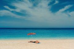 Retired man on sandy beach sunbathing on Mediterranean sea. Carefree elderly man sun tanning on sandy beach in shade of striped umbrella with beautiful stock photos