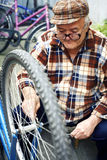 Retired man serviced bikes. Seniors-occupation, bicycle Royalty Free Stock Images