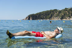 Retired man sleeping on bed in sea water Stock Photos