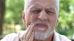 Retired man suffering from toothache, discomfort with implants, dental care. Stock photo royalty free stock photos