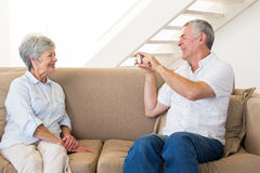 Retired man taking photo of his partner on the couch Royalty Free Stock Image
