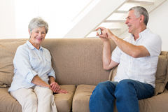 Retired man taking photo of his partner on the couch Royalty Free Stock Images