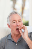 Retired man taking pills Royalty Free Stock Images