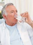 Retired man taking pills Royalty Free Stock Image