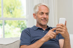 Retired man texting. Senior man sitting in couch reading text message on smartphone. Mature smiling man using smart phone at home. Portrait of happy retired man Stock Image