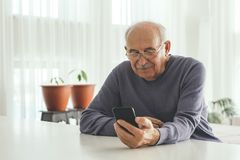 Retired man using computer technologies at home royalty free stock photos