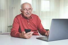 Retired man using computer technologies at home royalty free stock photography