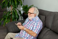 Retired man with a mobile in his home. Retired man with white beard and a mobile in his home Royalty Free Stock Images