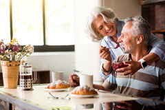 Retired man and woman having breakfast in the kitchen royalty free stock photo