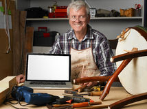 Retired man at work. Close-up portrait of senior carpenter at work. Old retired man sitting at his workshop behind  white screen laptop and reparing the chair Royalty Free Stock Images