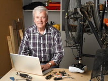 Retired man at work. Portait of active retired man sitting in front of laptop at bike repair shop while reparing bicycle. Small business Royalty Free Stock Images