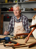 Retired man at work. Portrait of senior carpenter working at his worshop. Retired joinery owner sitting at desk and writing while repairs the seat. Small Stock Images