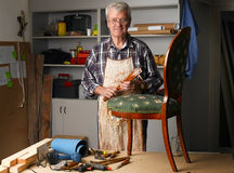 Retired man at work. Portrait of senior carpenter working at his worshop. Retired joinery owner sitting at desk and writing while repairs the seat. Small Royalty Free Stock Image