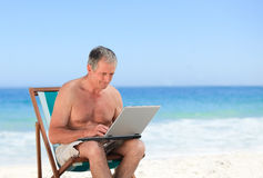 Retired man working on his laptop on the beach Royalty Free Stock Photo