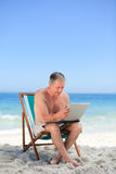 Retired man working on his laptop on the beach Stock Image