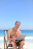 Retired man working on his laptop on the beach Stock Images