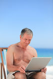 Retired man working on his laptop on the beach Royalty Free Stock Images