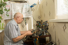 Retired man working at home on his handicrafts Stock Photography