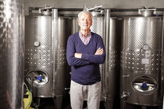 Retired man working. Portrait of retired winemaker standing at his cellar in front of stainless steel vessel while looking at camera and smiling Stock Photography