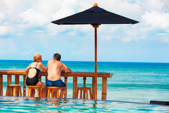 Retired mature couple relaxing beach swimming pool royalty free stock photos
