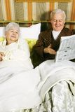 Retired Morning. A retired couple discussing the latest news in their bed in the morning while reading a news paper Stock Images