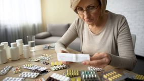 Retired obsessed with self-medication female reading medicine instruction. Stock photo stock photos
