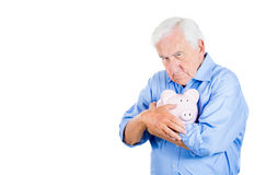Retired old man holding a piggy bank, looking very serious and possessive of his savings Royalty Free Stock Photos