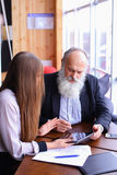 Retired old men learn new technology tablet with beautiful young. Retired old men deal with financial issues by using tablet technology and assistance fromrstate stock photography