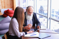 Retired old men learn new technology tablet with beautiful young. Retired old men deal with financial issues by using tablet technology and assistance fromrstate stock photo