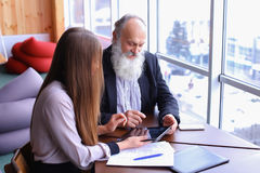 Retired old men learn new technology tablet with beautiful young. Retired old men deal with financial issues by using tablet technology and assistance fromrstate stock image