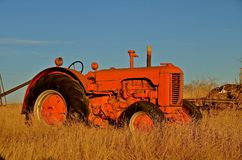Retired old orange tractor. An old orange tractor is left abandoned in a field of weeds Royalty Free Stock Image