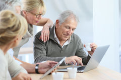 Retired people at home with laptop and tablet Stock Photography