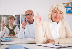 Retired people raising hands. Photo of retired people raising their hands during lesson Stock Photos