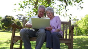 Retired people using a laptop. In a park stock footage
