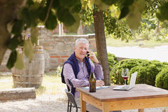 Retired professional man. Portrait of retired winemaker sitting at vineyard in front of his laptop and making call while tasting wine. Small business Royalty Free Stock Photos