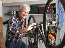 Retired professional. Portrait of retired man working at his workshop. Senior professional repairing bike in his bike shop. Small business Royalty Free Stock Photo