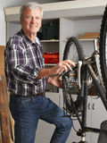 Retired professional. Portrait of retired man working at his workshop. Senior professional repairing bike in his bike shop. Small business Stock Images