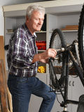 Retired professional. Portrait of retired man working at his workshop. Senior professional repairing bike in his bike shop. Small business Royalty Free Stock Images