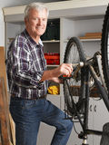 Retired professional. Portrait of retired man working at his workshop. Senior professional repairing bike in his bike shop. Small business Royalty Free Stock Photography