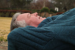 Retired and relaxed. Seniors retired man lying on back sleeping in park Royalty Free Stock Images