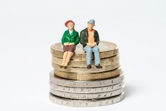 Retired. / elderly couple sitting on euro coins Royalty Free Stock Image