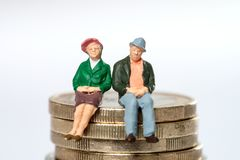 Retired. / elderly couple sitting on euro coins Royalty Free Stock Photography
