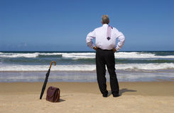 Retired senior business man on beach vacation, copy space. Retired senior man standing on a beach and looking at horizon Royalty Free Stock Images