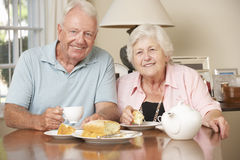Retired Senior Couple Enjoying Afternoon Tea Together At Home Stock Images