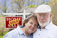 Retired Senior Couple in Front of Sold Real Estate. Happy Affectionate Senior Couple Hugging in Front of Sold Real Estate Sign and House Royalty Free Stock Images