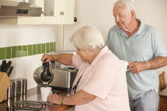 Retired Senior Couple In Kitchen Making Hot Drink Together Royalty Free Stock Photography
